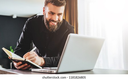 Young bearded businessman is standing by computer, looking at laptop screen, making notes in notebook. Man is watching a webinar, recording information. Online marketing, adult education, e-learning.