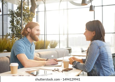 Young bearded businessman talking to young businesswoman while working on laptop computer at the table during meeting in cafe