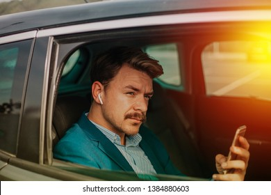 Young bearded businessman texting in the backseat of a limo.
