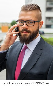 Young bearded businessman wearing eyeglasses using mobile phone outside the office