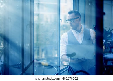 Young Bearded Businessman Wearing Glasses White Shirt Waistcoat Holding Modern Laptop Hands Looking Panoramic Windows.Man Working Office Startup Project Workplace.View Through Window.Blurred