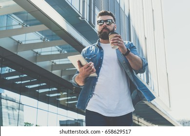 Young bearded businessman wearing sunglasses walking down city street, holding cup of coffee and tablet computer. In background is modern glass building. Man hurries to business meeting. Lifestyle.
