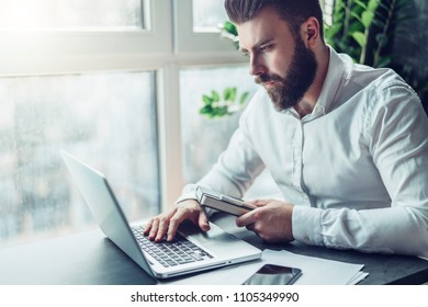 Young bearded businessman in white shirt is sitting at table and working on laptop. Freelancer works at home. Student is studyng online. Online marketing, education, blogging. Business planning.
