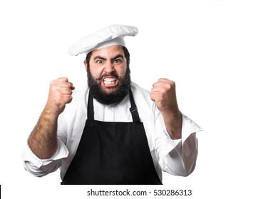 Young bearded chef angry or banging on someone isolated on white background