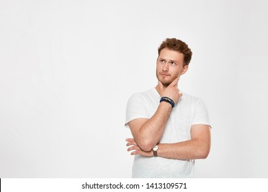 Young bearded confident man with hand raised on chin and looking aside while standing against white background expressing thoughtful emotion.