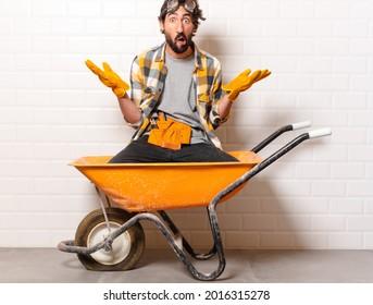 young bearded construction worker man on a wheelbarrow