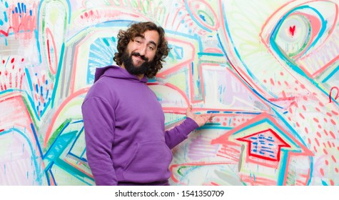 young bearded crazy man feeling happy and cheerful, smiling and welcoming you, inviting you in with a friendly gesture against graffiti wall