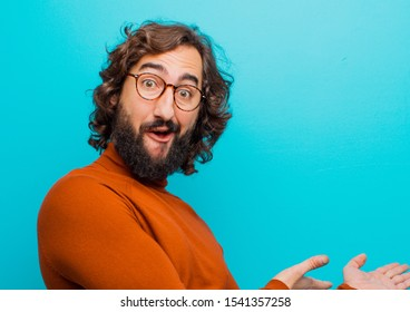 young bearded crazy man feeling happy and cheerful, smiling and welcoming you, inviting you in with a friendly gesture against flat color wall