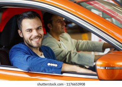 Young bearded dealer sitting next to handsome client in car in showroom. Manager wearing in blue jacket and white t-shirt, sitting inside vehicle, smiling and looking at camera from open car window.