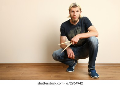 Young bearded drummer with drumsticks in hand on a beige background