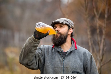 Young bearded farmer drinking fresh apple juice