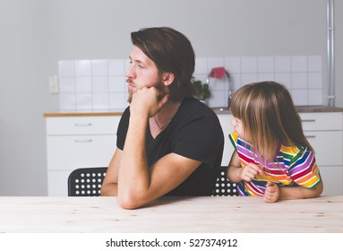 Young bearded father looking tired and ignoring his kid in preschool age indoors