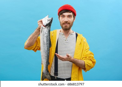 Young bearded fishmonger selling huge fish pointing with hand at it, advising customers to buy it. Positive handsome man dressed casually posing at camera with smile while holding big salmon