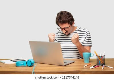 young bearded graphic designer with a laptop with an angry, aggressive and menacing pose, ready for the fight, showing fists furiously and belligerently.
