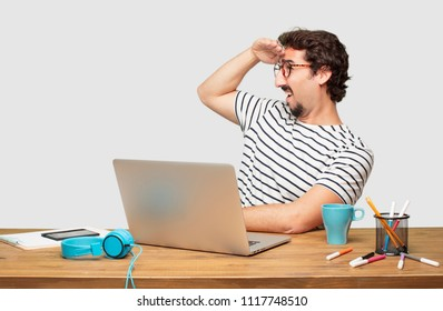 young bearded graphic designer with a laptop looking far off into the distance, searching for a distant object with a confused look. Lateral or side view.