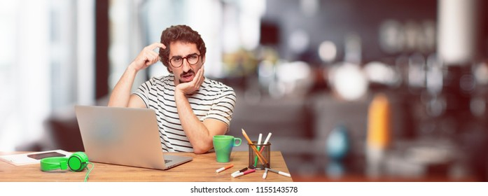 young bearded graphic designer with a laptop with a goofy, dumb, silly look, feeling shocked and confused at a recent realization, not really understanding an idea.