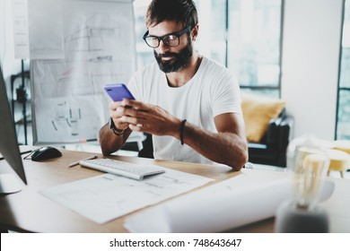 Young bearded graphic designer wearing eye glasses and working at modern loft studio-office.Man using smartphone.Blurred background. Horizontal