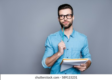 Young bearded guy in glasses holding a notebook and thinking about exams.