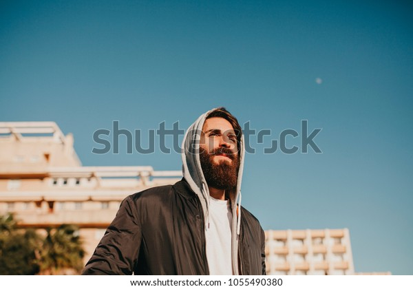 Young bearded guy portrait, with the sun in the face, with urban street style clothes