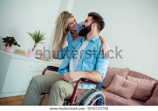 Young bearded handicapped man in wheelchair and his pretty wife