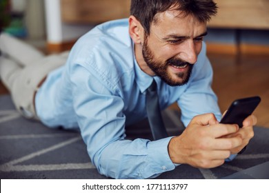 Young bearded handsome businessman lying on the floor at home and using smart phone.