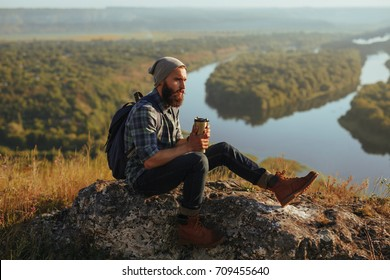 Young bearded hipster with backpack and cup of coffee sitting on rock with views of nature around.