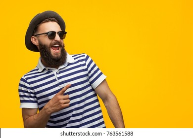 Young bearded hipster in cap and sunglasses pointing happily away on orange background.