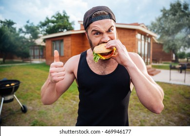 Young bearded hipster guy biting delicious burger and showing thumbs up outdoors