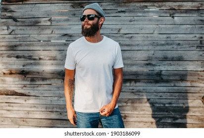 Young bearded hipster guy wearing white blank t-shirt. Mock-up for print. T-shirt template.