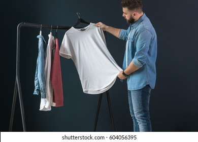 Young bearded hipster man dressed in denim shirt, stands near counter with clothes against dark wall, holds white T-shirt on clothes hanger and looks at it. Man is choosing clothes. Shopping.
