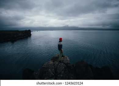 Young bearded hipster man in red fisherman beanie and blue woolen traditional sweater, sailor or explorer stands on edge of rock or cliff, looks at sea, ocean or horizon on cloudy, rainy gloomy day