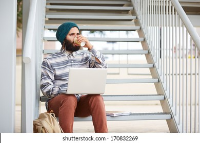Young bearded hipster student using computer and drinking coffee at university campus