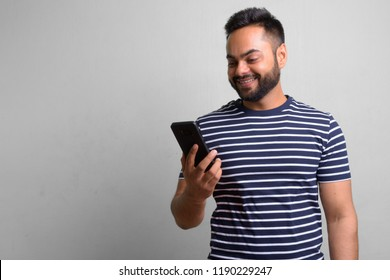 Young bearded Indian man against white background