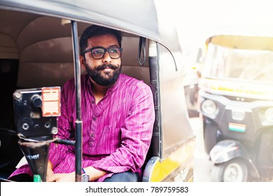 Young bearded indian man sitting in rickshaw