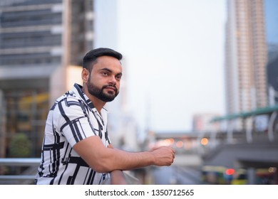 Young bearded Indian man thinking and looking at view of the city outdoors