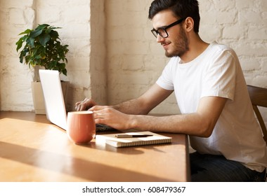 Young bearded journalist in eye glasses write new article in the internet and answer questions of his readers. Man in sunny day at home surfing social network and read news. Happy guy working indoor.