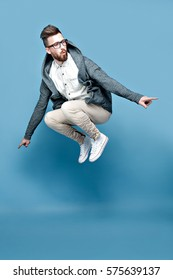 Young bearded male in casual clothing in moment of jump isolated in blue studio background.