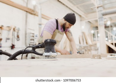 A young bearded male joiner uses random orbit sander, processes wooden products to produce furniture in carpenter workshop