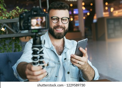 Young bearded male video blogger creates video content for his channel. Happy guy shoots video streaming for users while sitting in coffee shop. Man vlogger relieves himself on camera with tripod.