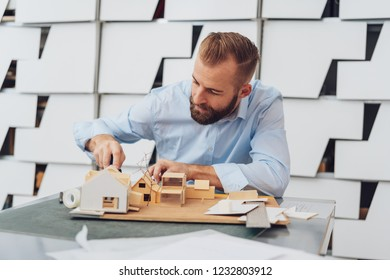 Young bearded man architect is working on wooden 3D model of house, sitting at the desk in office with modern interior design