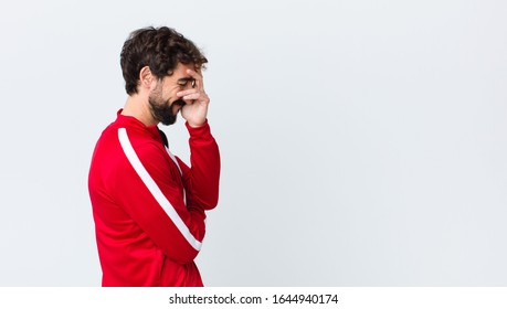 young bearded man back view looking stressed, ashamed or upset, with a headache, covering face with hand against copy space wall