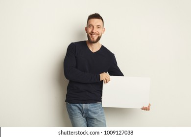 Young bearded man with blank white banner. Smiling man holding advertising sheet, copy space, isolated