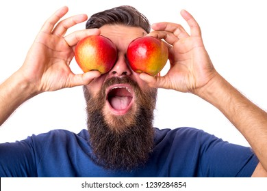 Young bearded man in blue tshirt holding red apples in front of his eyes making funny face. Isolated on white background, portrait
