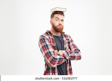 Young bearded man with book on his head having fun over white background