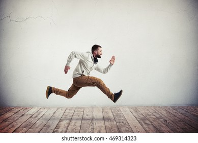 Young bearded man in casual clothes is photographed in mid-air running pose over wooden floor and white wall background