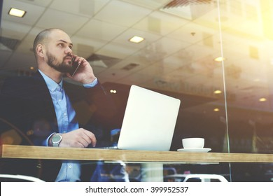 Young bearded man CEO of big successful company is having mobile phone conversation with customers, while is sitting with portable laptop computer in modern restaurant interior during work break