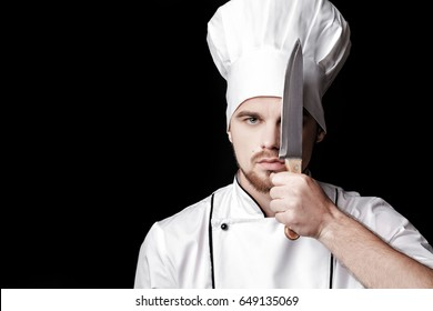 Young bearded man chef In white uniform holds  knife in front of face on  black background
