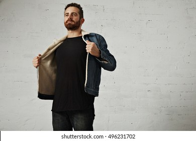 Young bearded man in denim jacket with shearling liner shows his chest wearing black unlabeled henley shirt longsleeve, isolated on white brick wall in club
