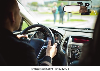 young bearded man driving a car, inside cabin rides, looking at road, driving, holding steering wheel.