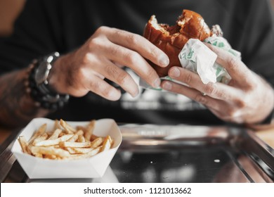Young bearded man eating burger and french fries close up.